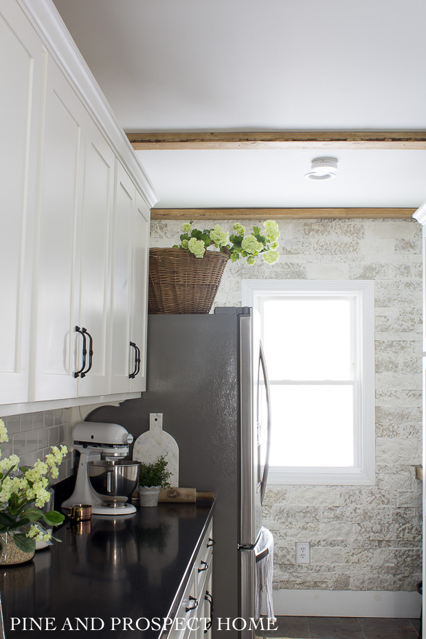 We love the stone feature wall in our white cottage style kitchen