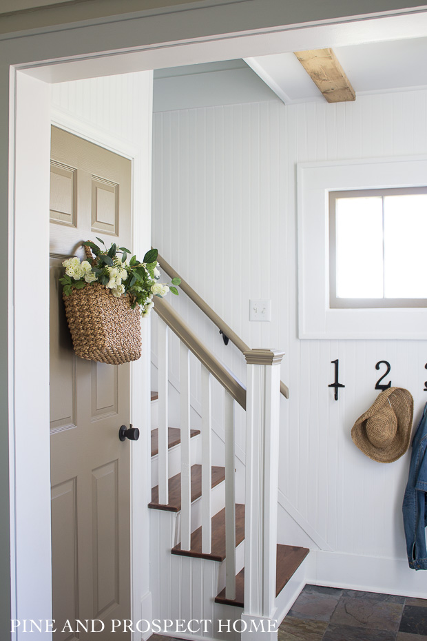 A warmer hue on the door and railings contrasts beautifully against the white beadboard